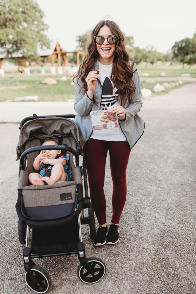 a woman in workout attire with long dark hair holding beef snacks next to a baby in a stroller