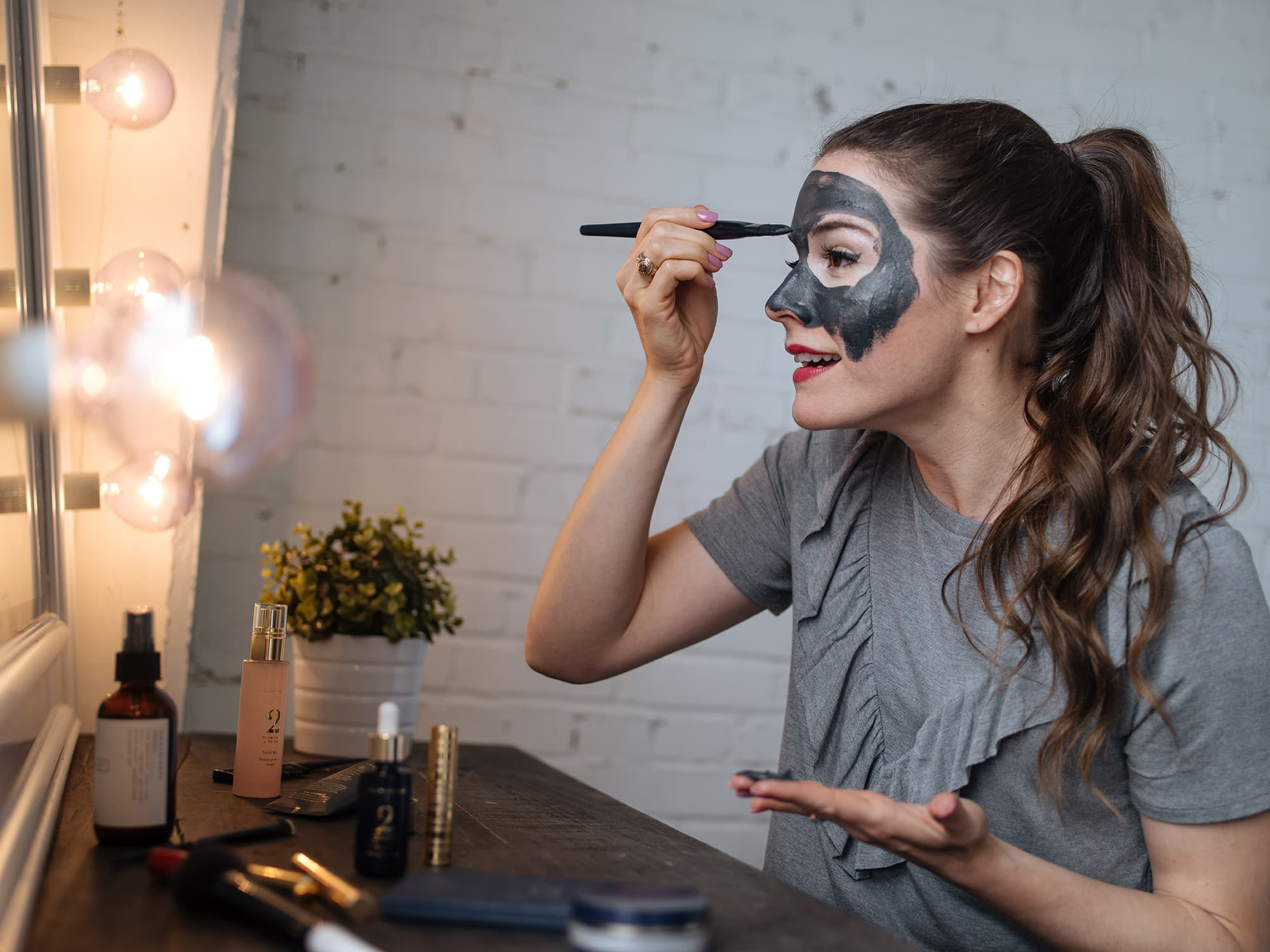 woman putting on a charcoal mask with a brush in front of a lighted mirror - spa day at home