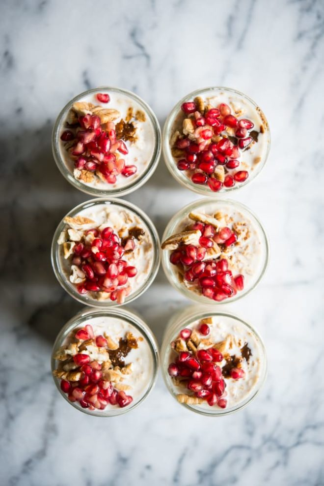 6 glass mason jars filled with overnight oats and topped with pecans and pomegranate seeds on a marble surface