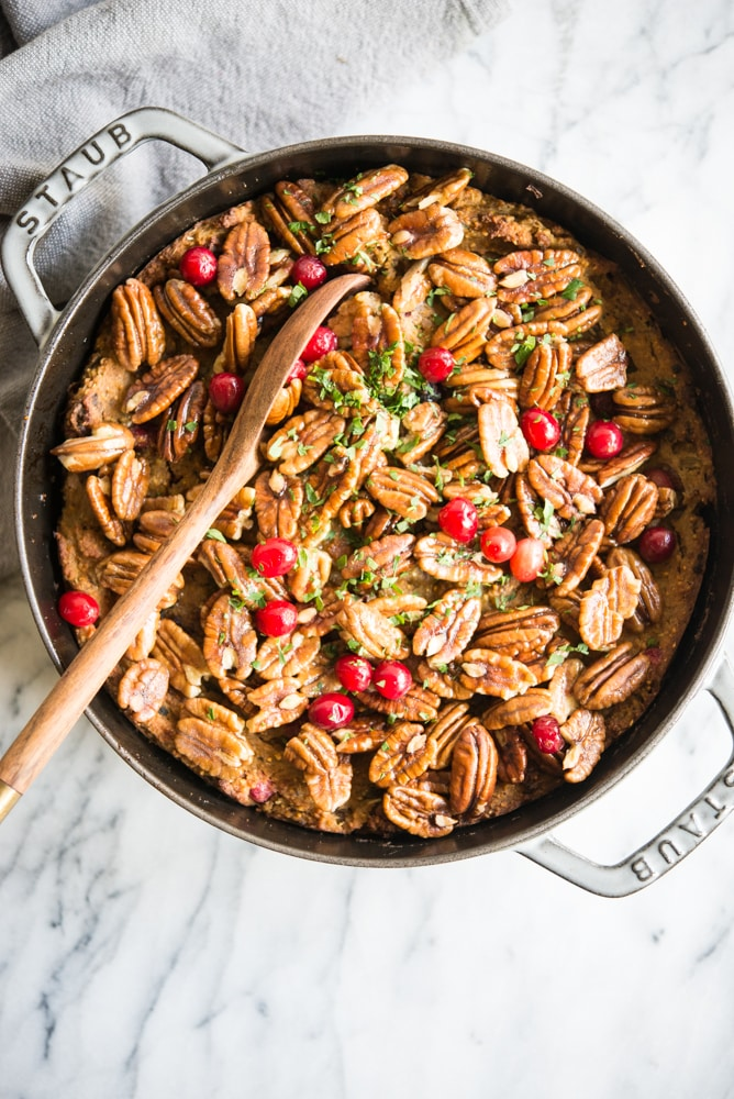 overhead view of a casserole dish sitting on top of a white marble table with a wooden spoon dipped in filled with bacon cranberry cornbread stuffing with candied pecans, cranberries and chopped parsley on top