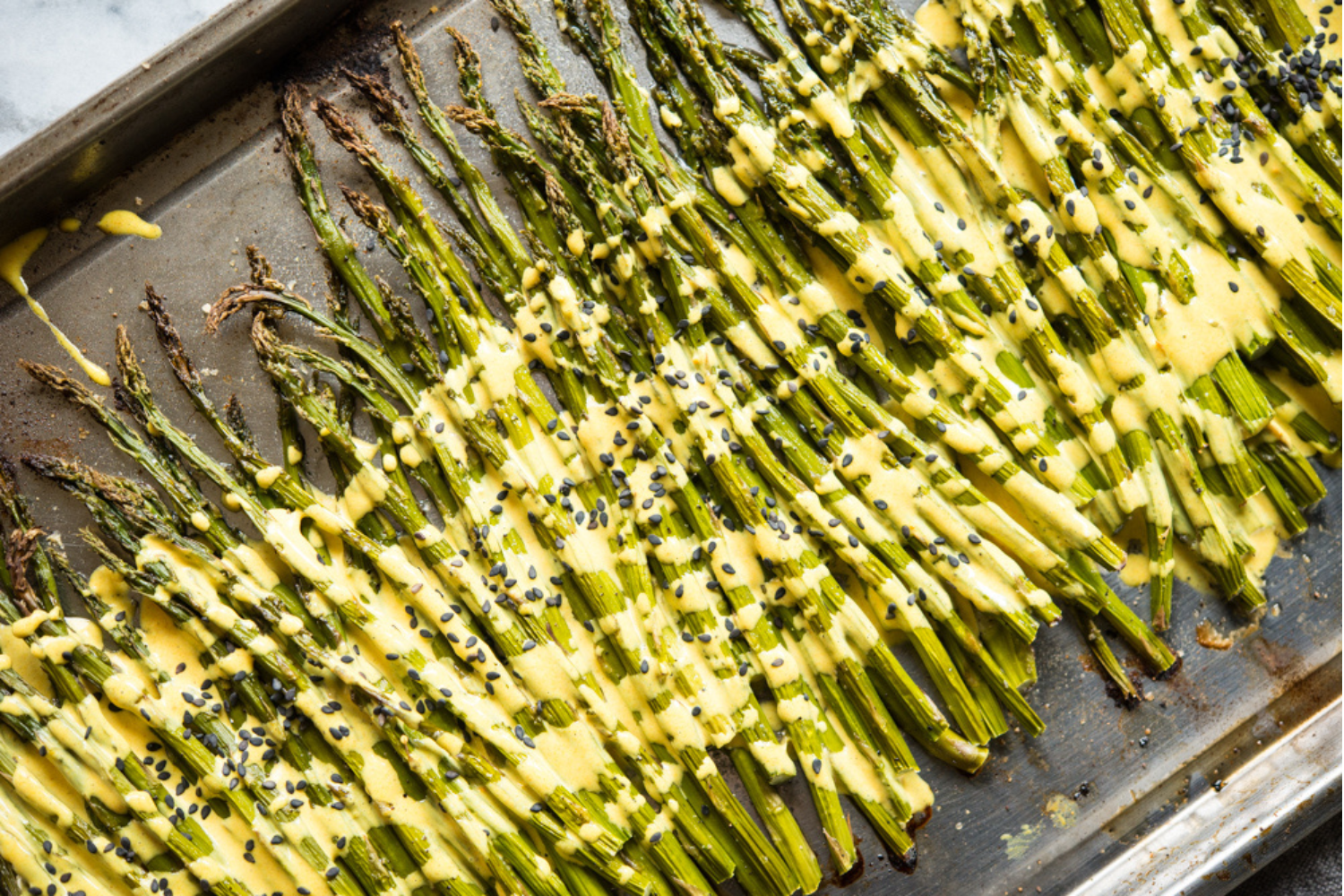 roasted asparagus on a stainless steel sheet pan with a bright yellow lemon cardamom sauce poured over top and garnished with black sesame seeds