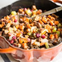 paleo stuffing with sweet potatoes, sausage, and cranberries in a pumpkin-shaped cast iron pot on a marble surface