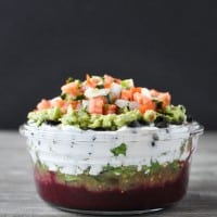 glass bowl filled with 7 layer dip and topped with pico de Gallo on a wood table