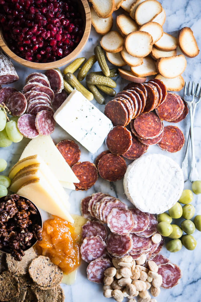 Charcuterie board with meats, cheeses, honey, nuts, a wooden bowl of pomegranates, olives, grapes, pickles, crackers, on a marble board