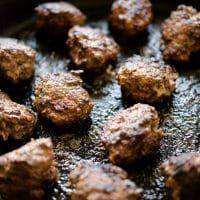 a cast iron skillet filled with chicken liver meatballs