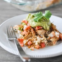 a white plate of chicken taco casserole with guacamole on top