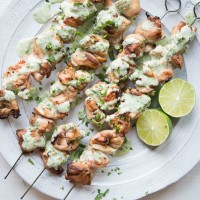 overhead view of skewers of Citrus Chicken with Cilantro Garlic Sauce on a white plate