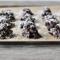Chocolate Chili Pecan Clusters on a parchment lined baking sheet with coconut flakes on top