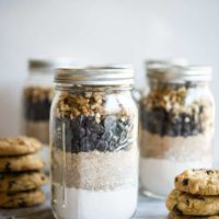 Gluten free chocolate chip cookie mix in mason jars on a marble slab surrounded by chocolate chip cookies