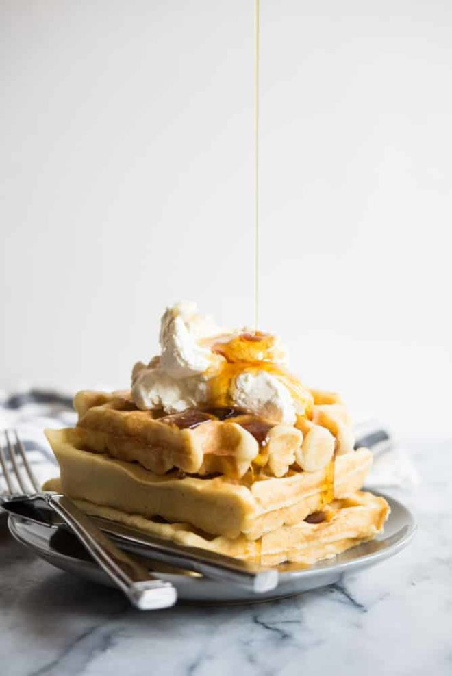 gluten free overnight waffles with whipped cream and a syrup drizzle