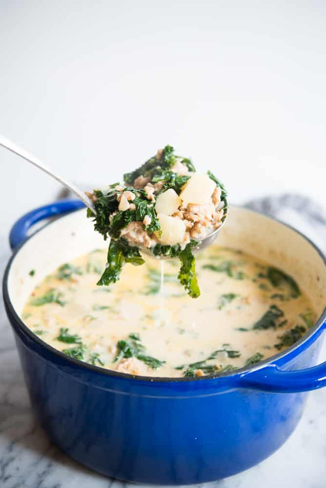 creamy kale and sausage soup in a blue pot on a marble background