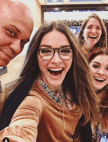 "a ""selfie"" with three long haired smiling women and a bald man"