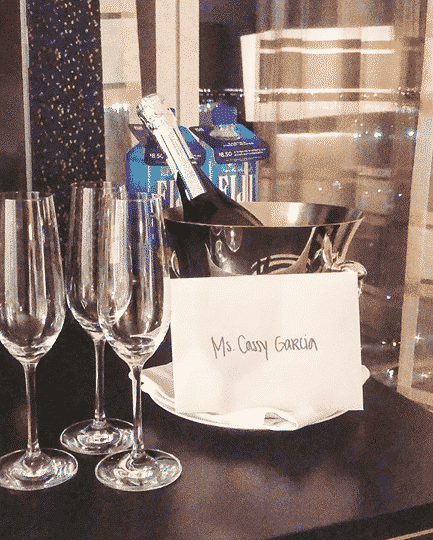 3 champagne glasses on a black table with a bottle of champagne chilled in an ice bucket and a card that reads Ms. Cassy Garcia