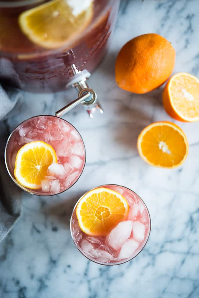 two cups of trash can punch with orange slices in it next to a pitcher and two orange halves, on a marble surface