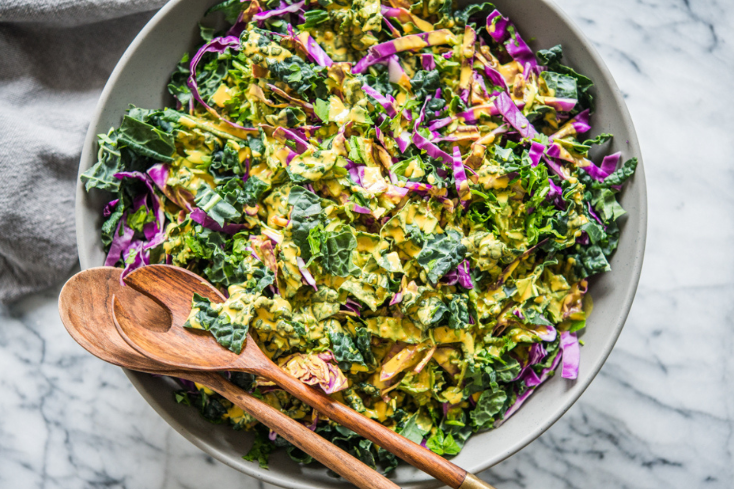 grey bowl on a marble surface filled with colorful kale and purple cabbae with a bright yellow dressing