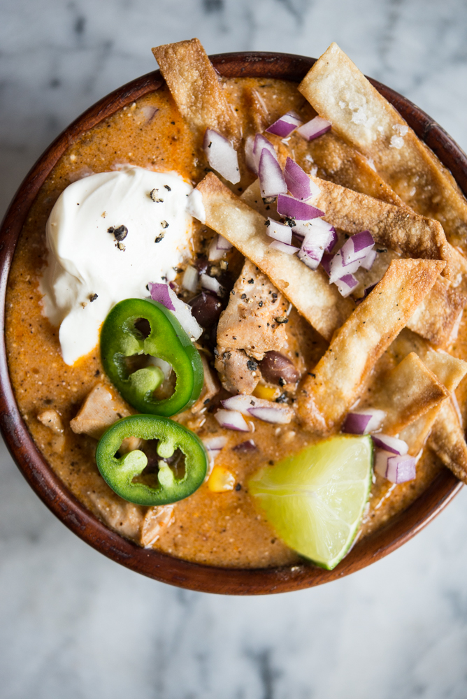 chicken enchilada soup in a wood bowl on a marble surface topped with tortilla strips, diced red onion, sliced jalapeno, and sour cream - crock pot freezer meals