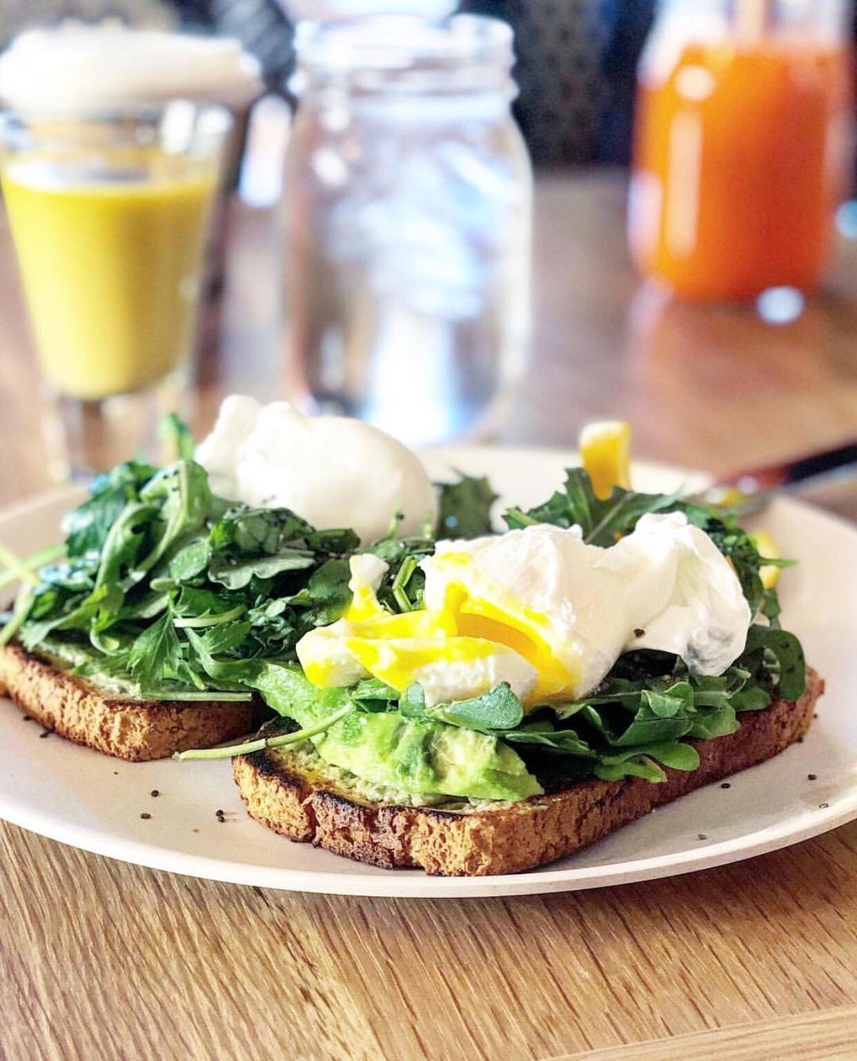 a plate of gluten free avocado toast with poached eggs on top at wellness retreat in phoenix