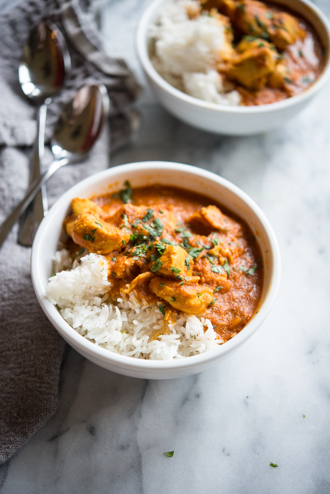 slow cooker freezer meal - chicken tikka masala over rice in a white bowl on a marble surface