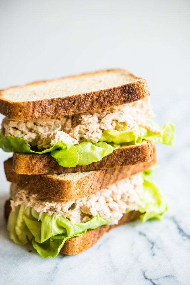 classic tuna salad sandwiches stacked on top of each other on top of a marble board