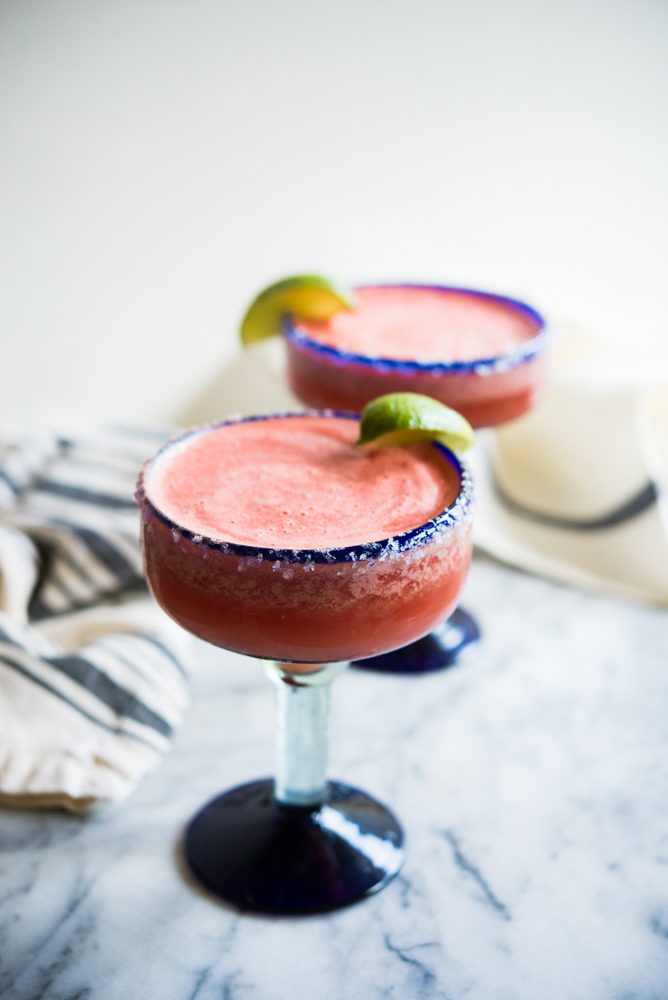 frozen watermelon margaritas in a blue-rimmed margarita glass with a salted rim and lime wedge on a marble surface