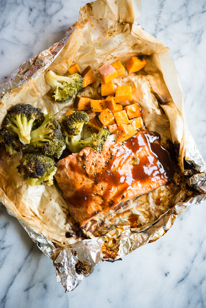 salmon, sweet potatoes, and broccoli florets seasoned with BBQ sauce in a foil and parchment paper packet on a marble countertop