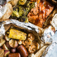 2 grilled foil packet dinners - shrimp, sausage, potatoes, and corn with cajun seasoning in a parchment and foil package and bbq salmon, sweet potatoes, and broccoli in a foil packet.