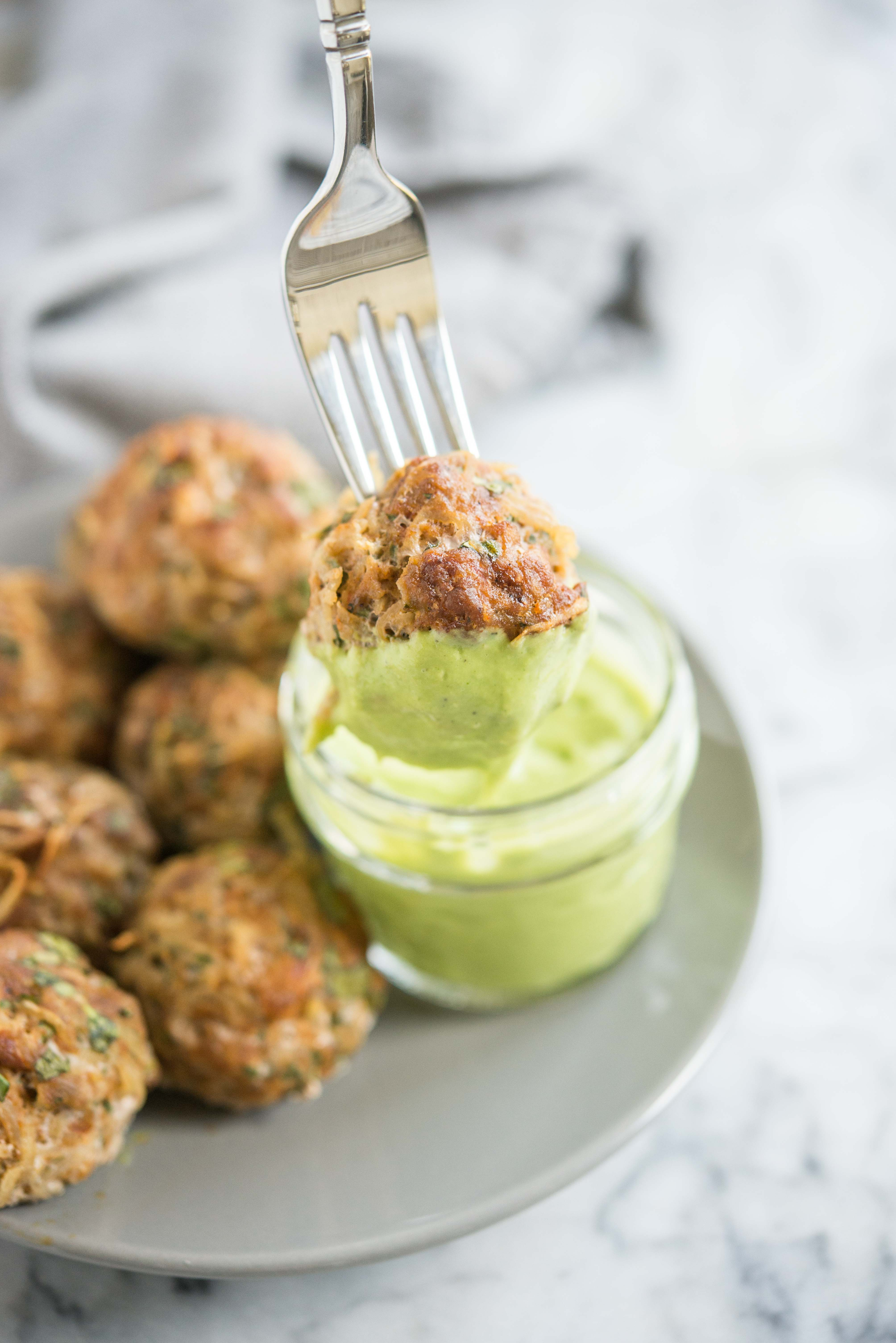 fork holding a chorizo potato breakfast meatball dipped in a bright green sauce