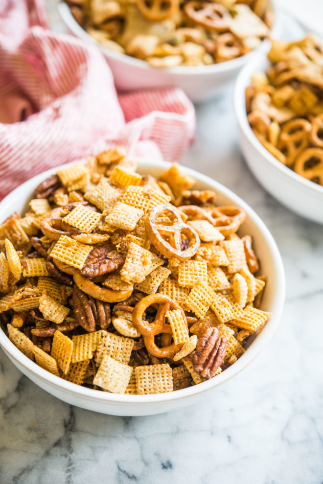 gluten free chex mix in a bowl on a marble board with a red and white striped napkin sitting behind it
