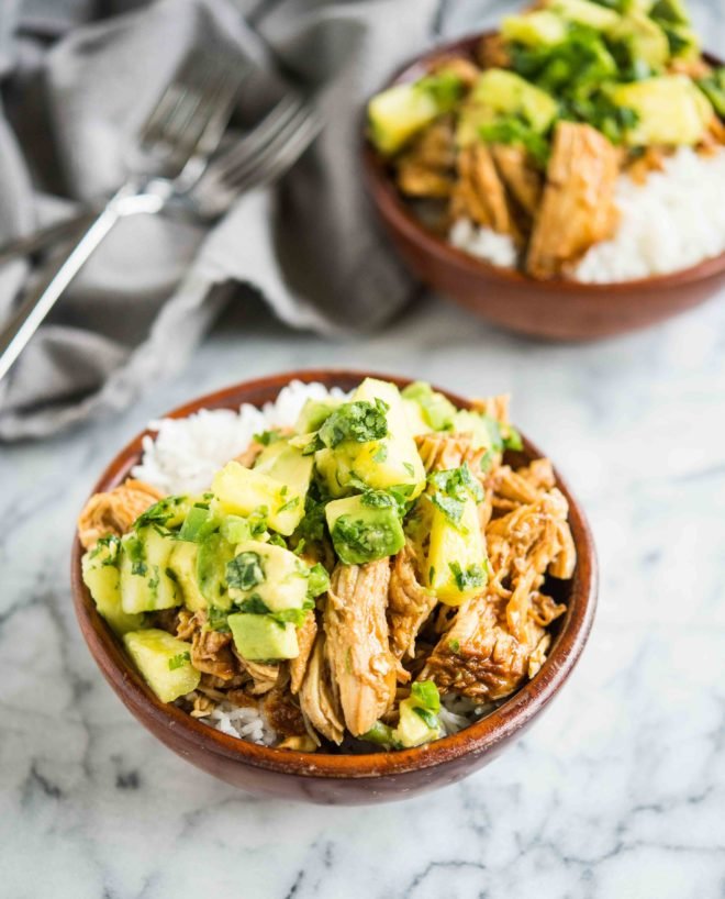 wooden bowls filled with white rice topped with Hawaiian chicken and pineapple avocado salsa on a marble board - healthy instant pot chicken recipe