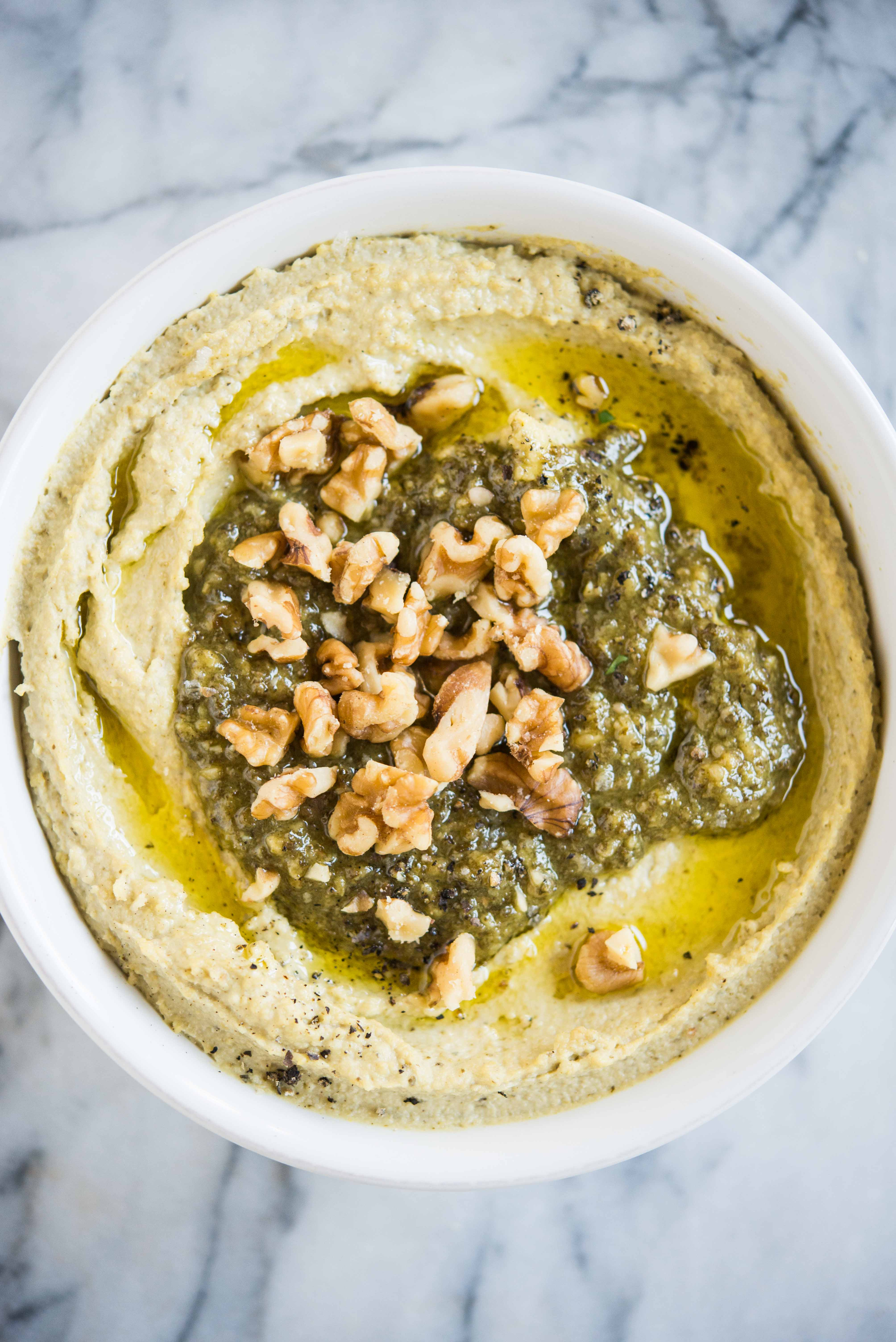 creamy hummus with pesto and walnuts on top in a white bowl on a marble surface