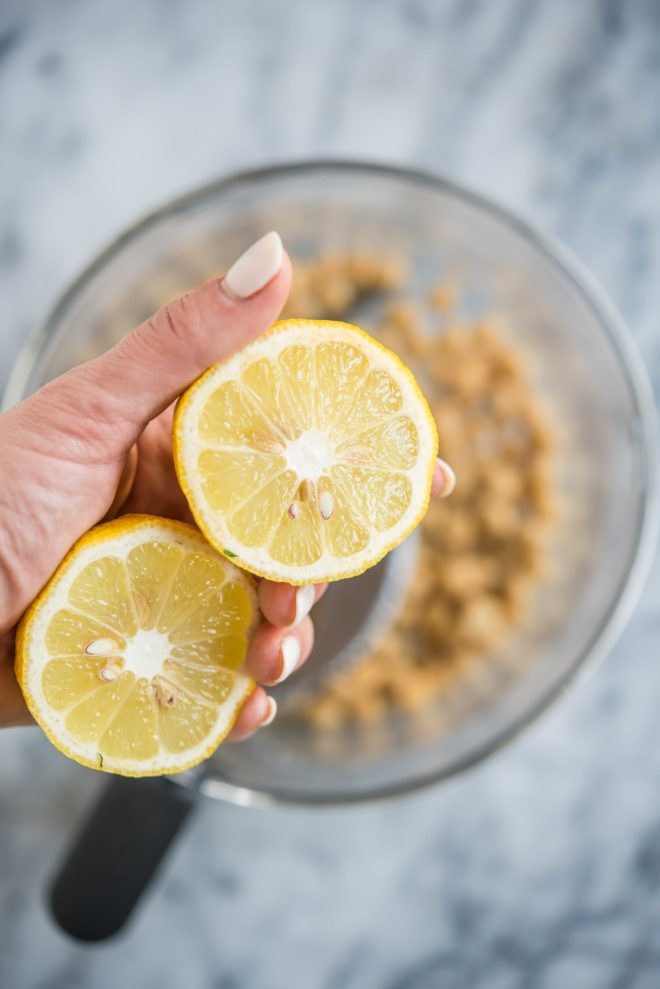 how to make hummus - woman's hand holding two lemon halves over a food processor