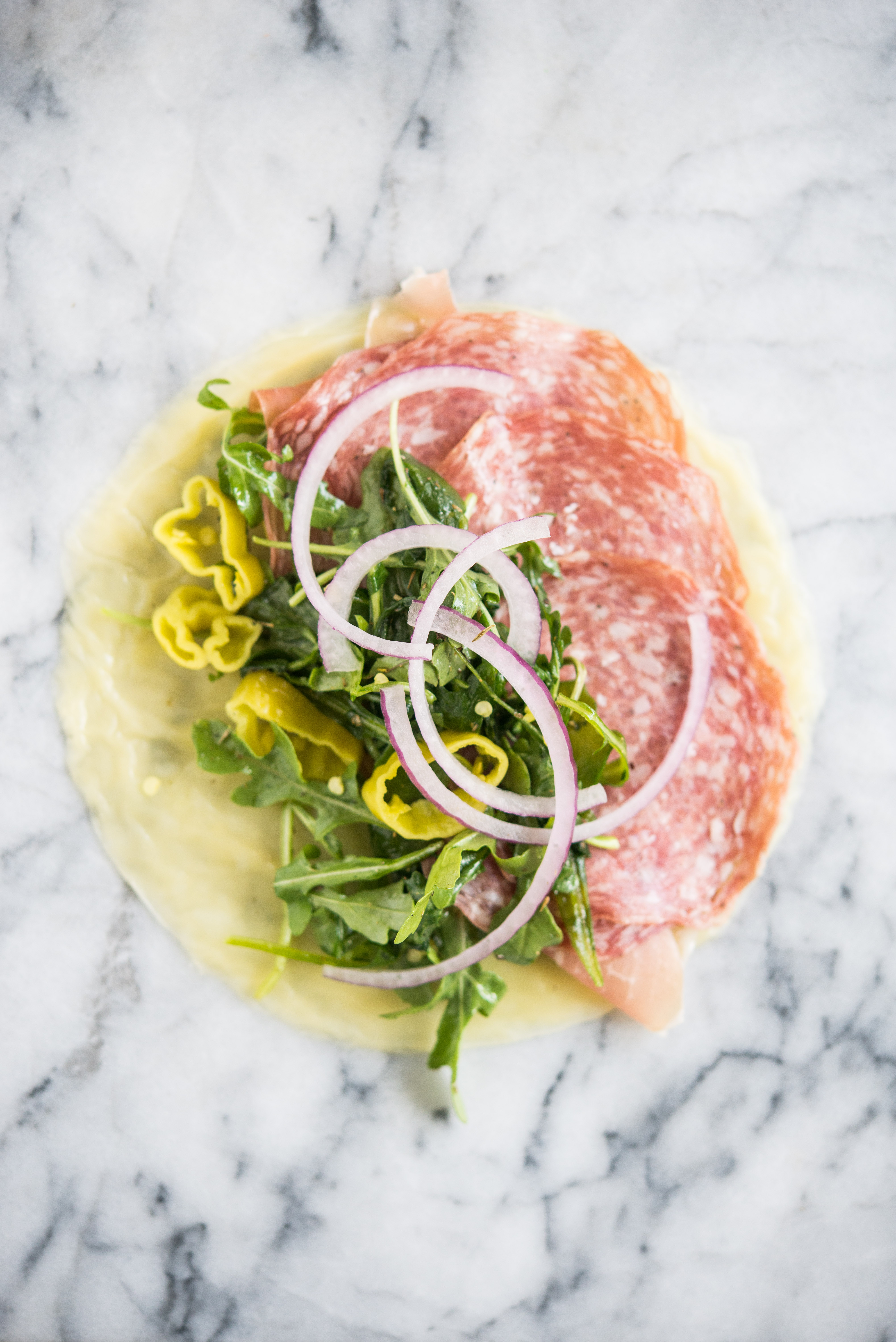 italian lunch meats, arugula, red onions, pepperonicini on a cheese wrap on a marble board