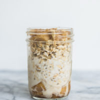 apple cinnamon overnight oats in a mason jar against a white wall sitting on a marble countertop