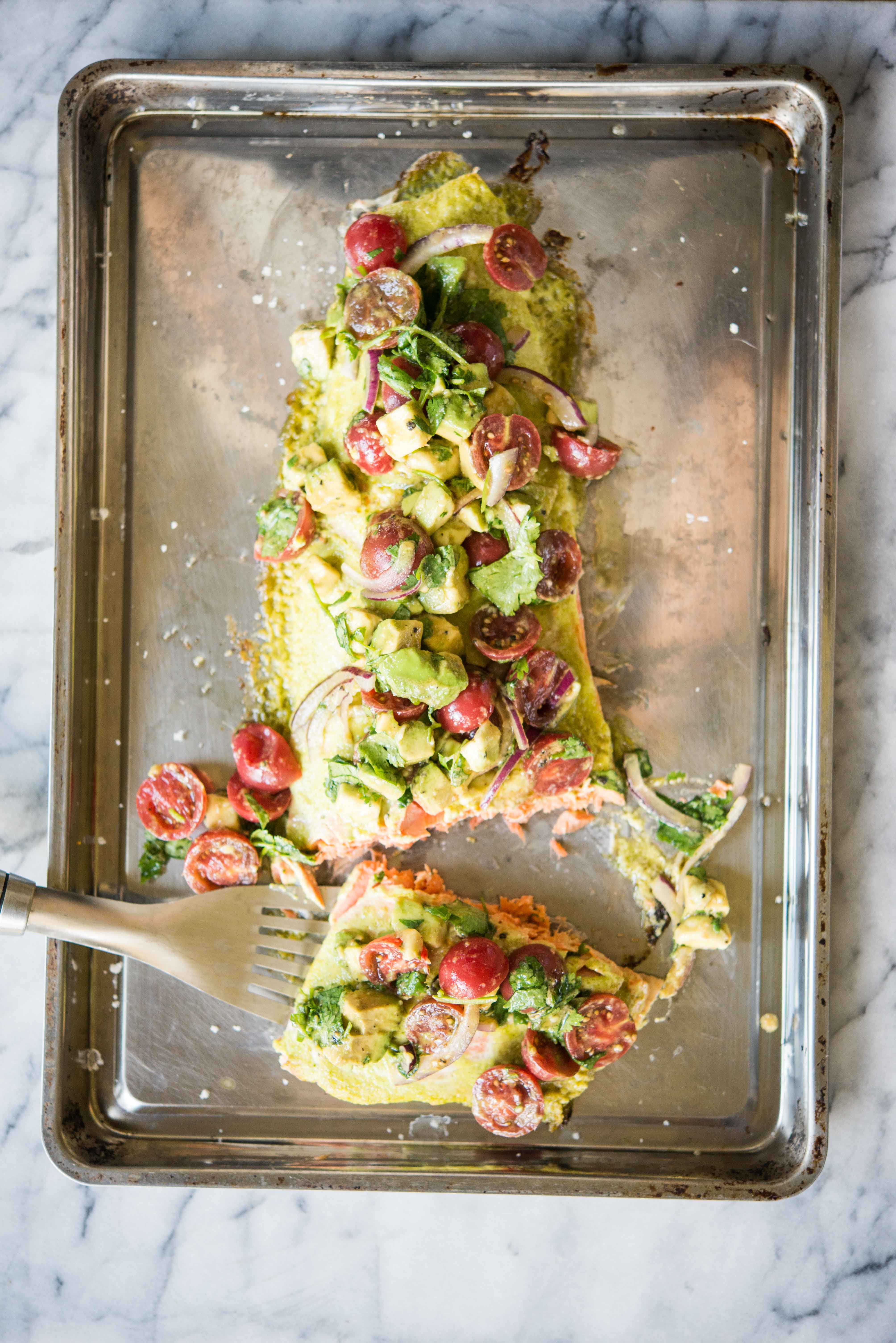 cilantro lime salmon bake topped with tomato avocado salsa on a sheet pan