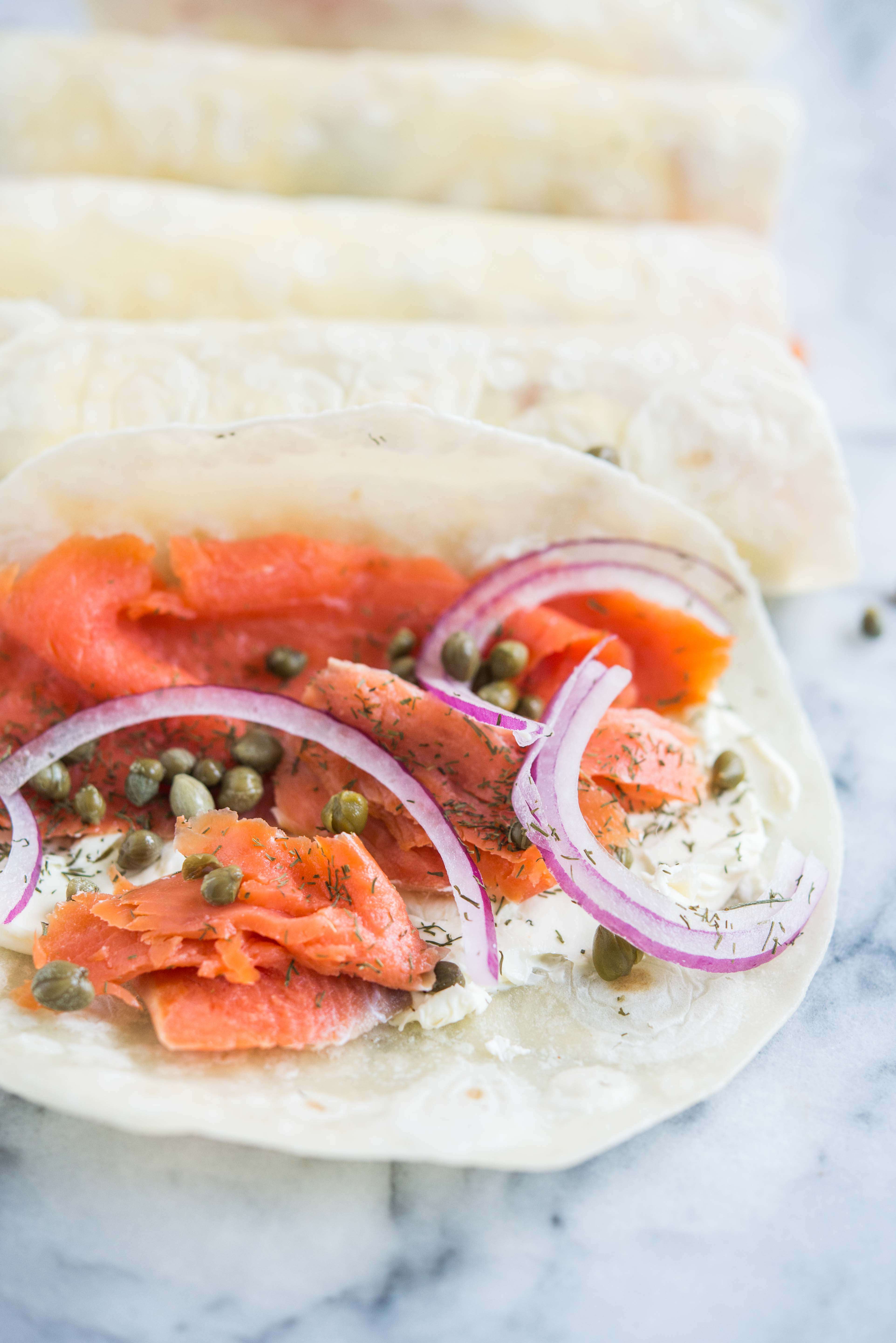 smoked salmon lunch wrap - tortilla smeared with cream cheese, smoked salmon, capers, and red onion, on a marble board