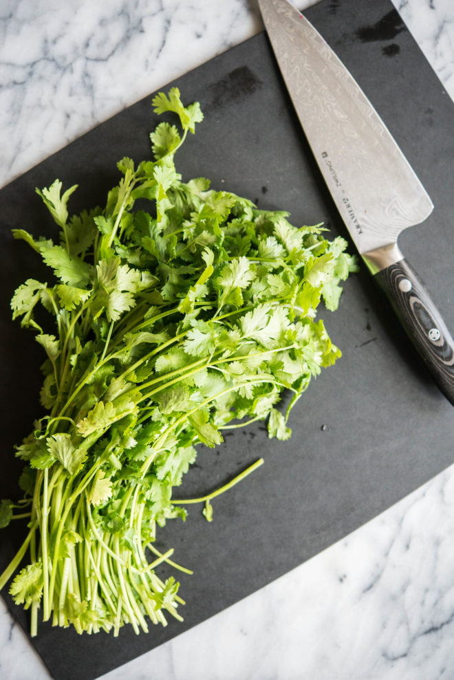 bunch of cilantro on a black cutting board next to a large knife