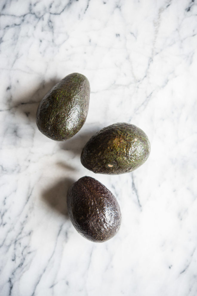 three avocados on a marble board