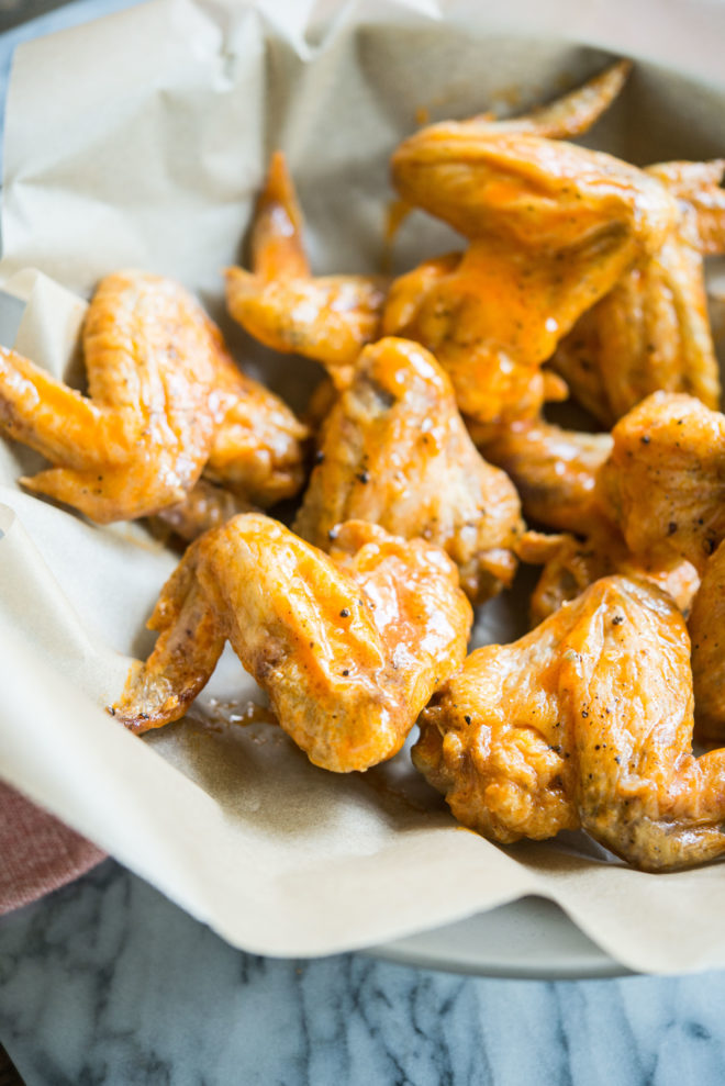 crispy baked buffalo chicken wings in a bowl lined with parchment paper