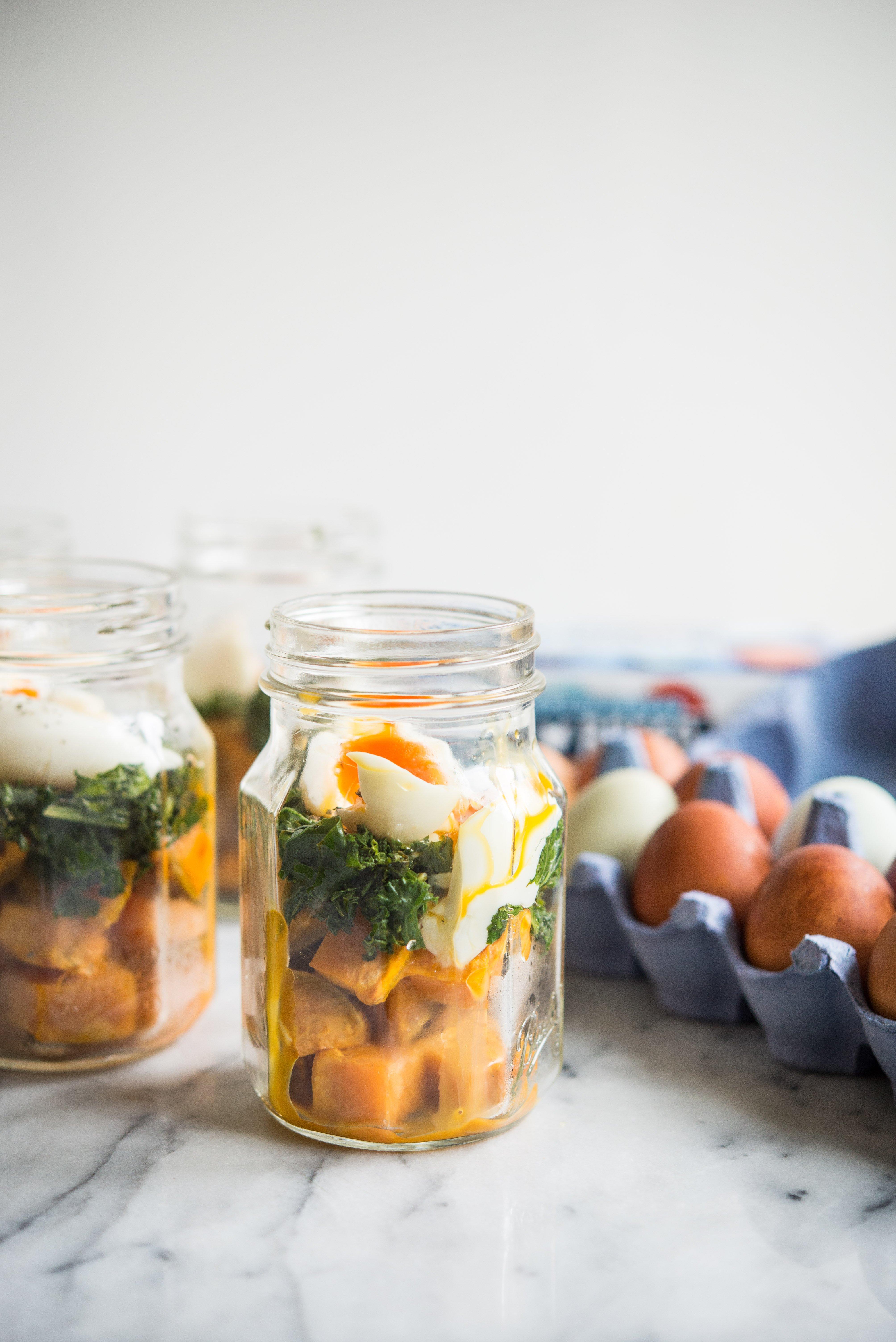 make-ahead balanced breakfast jars - sweet potatoes, kale, and soft boiled eggs in a mason jar on a marble board