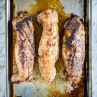 3 baked pork tenderloins on a stainless steel sheet pan
