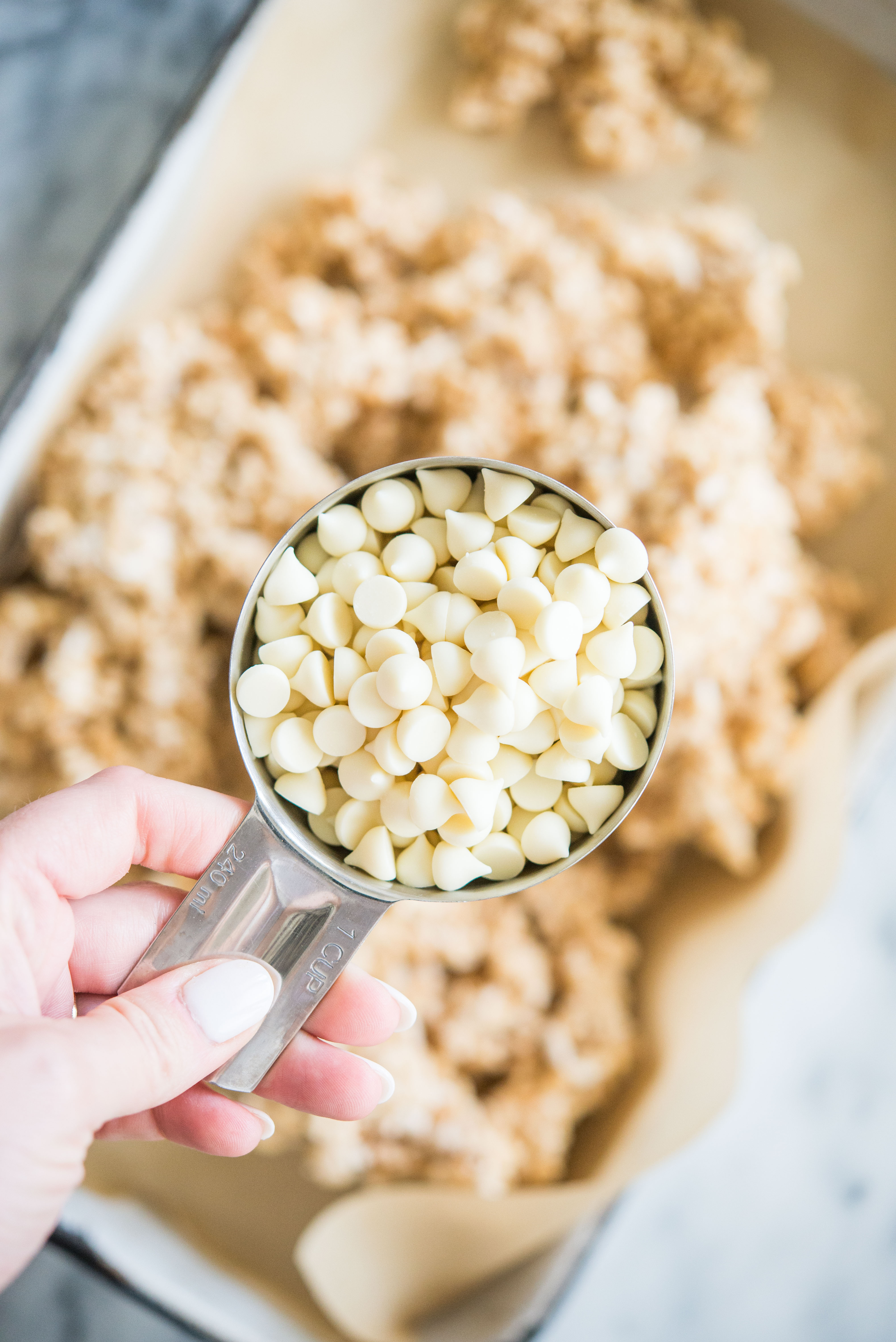white chocolate chips over a mixture of rice krispie treats