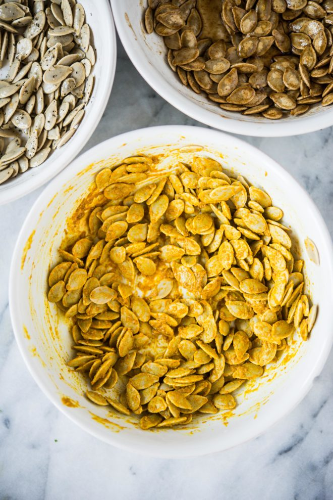 homemade pumpkin seeds tossed in curry seasoning in a white bowl