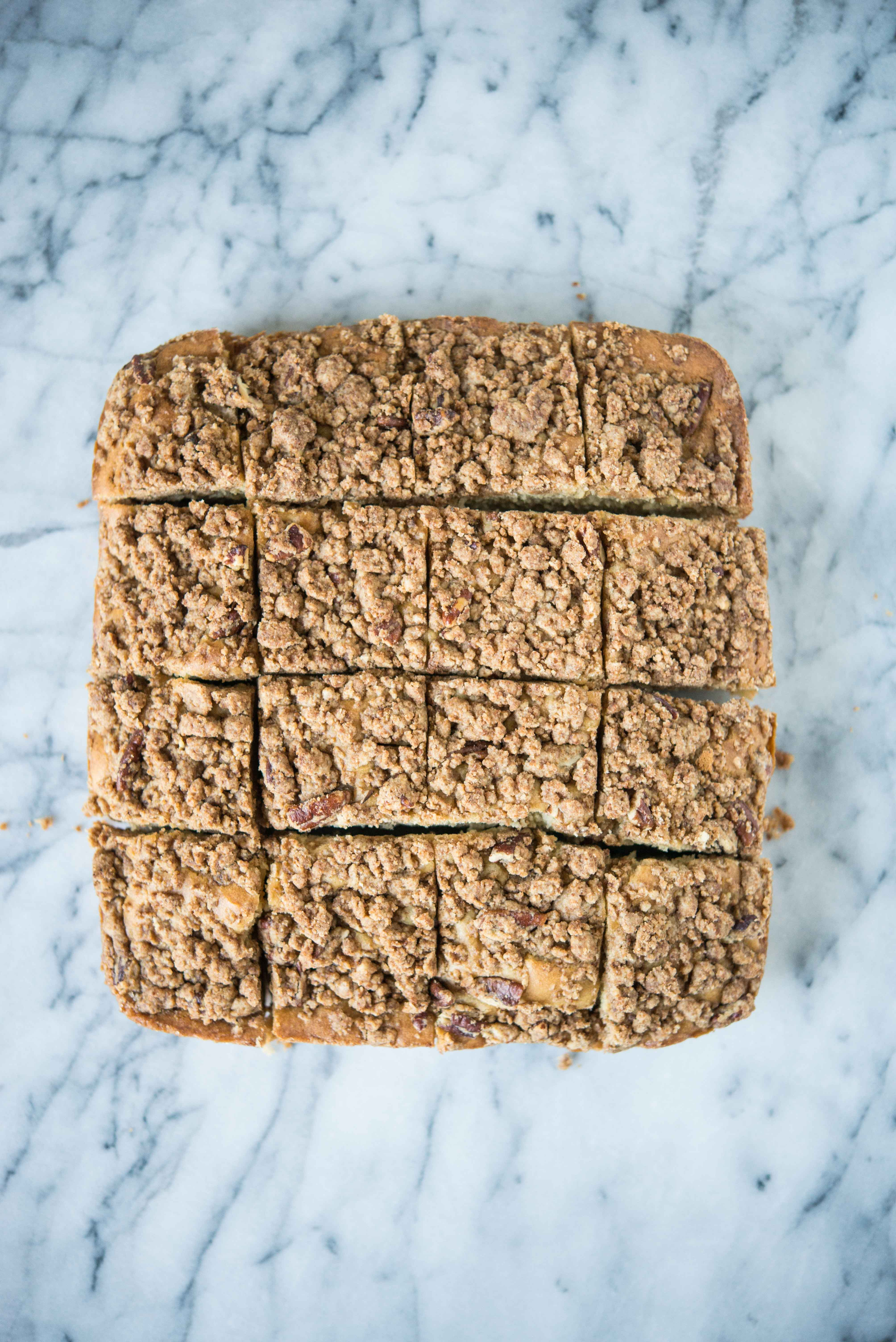 gluten free cinnamon coffee cake cut into 16 squares on a marble surface