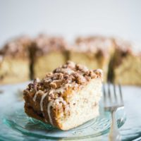 cinnamon coffee cake with icing drizzled on top on a glass plate with a fork sitting beside it on a marble surface