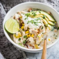easy white chicken chili in a bowl topped with lime, sour cream, avocado, and cilantro on a marble surface with a grey towel beside it