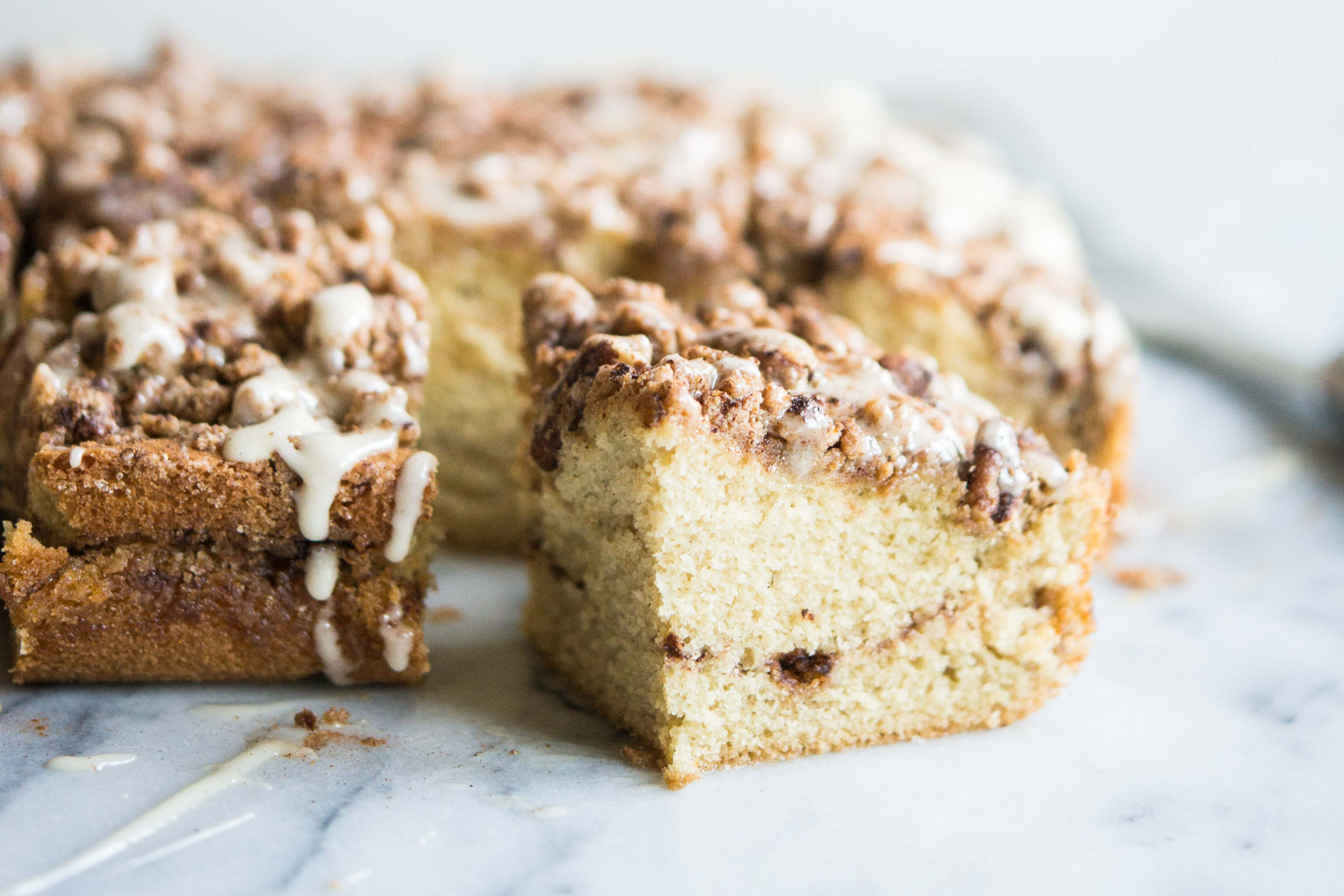 cinnamon roll coffee cake with a swirl of cinnamon sugar in the middle on a marble surface