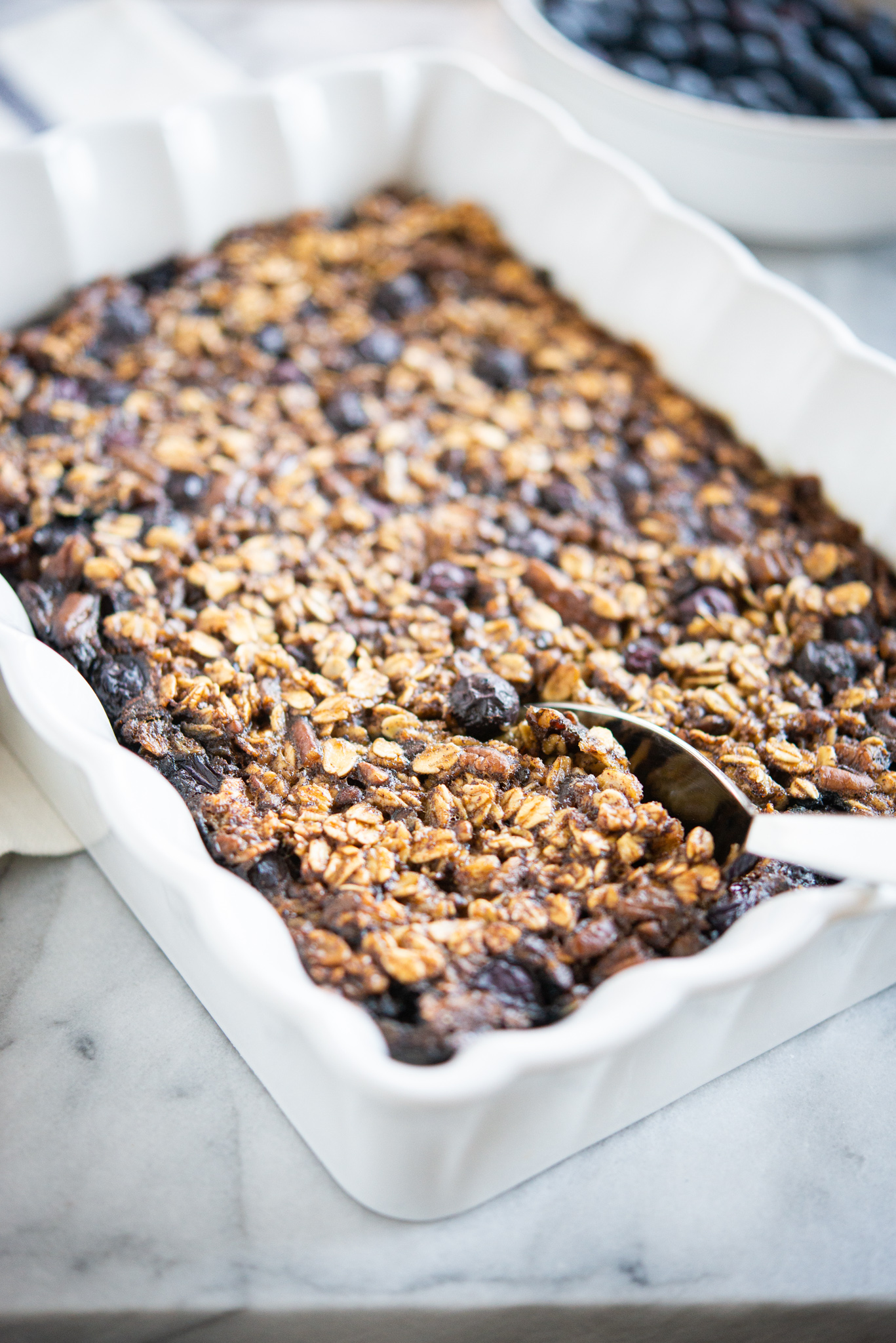 blueberry baked oatmeal in a white rectangular baking dish with a spoon in it on a marble surface