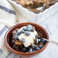 a square of blueberry oatmeal bake in a wooden bowl topped with yogurt and fresh blueberries on a marble surface