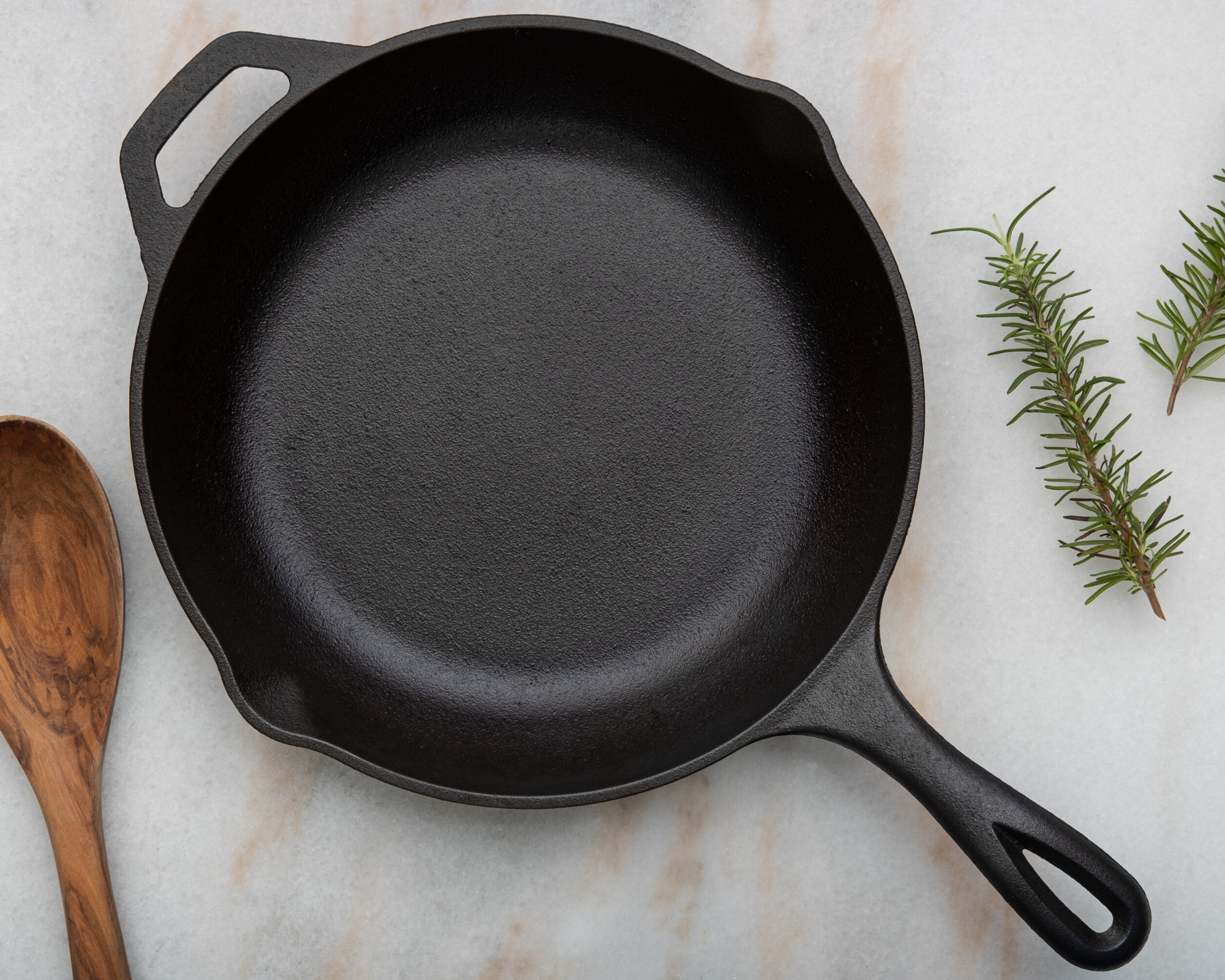 cast iron pan on marble surface with rosemary and wooden spoon