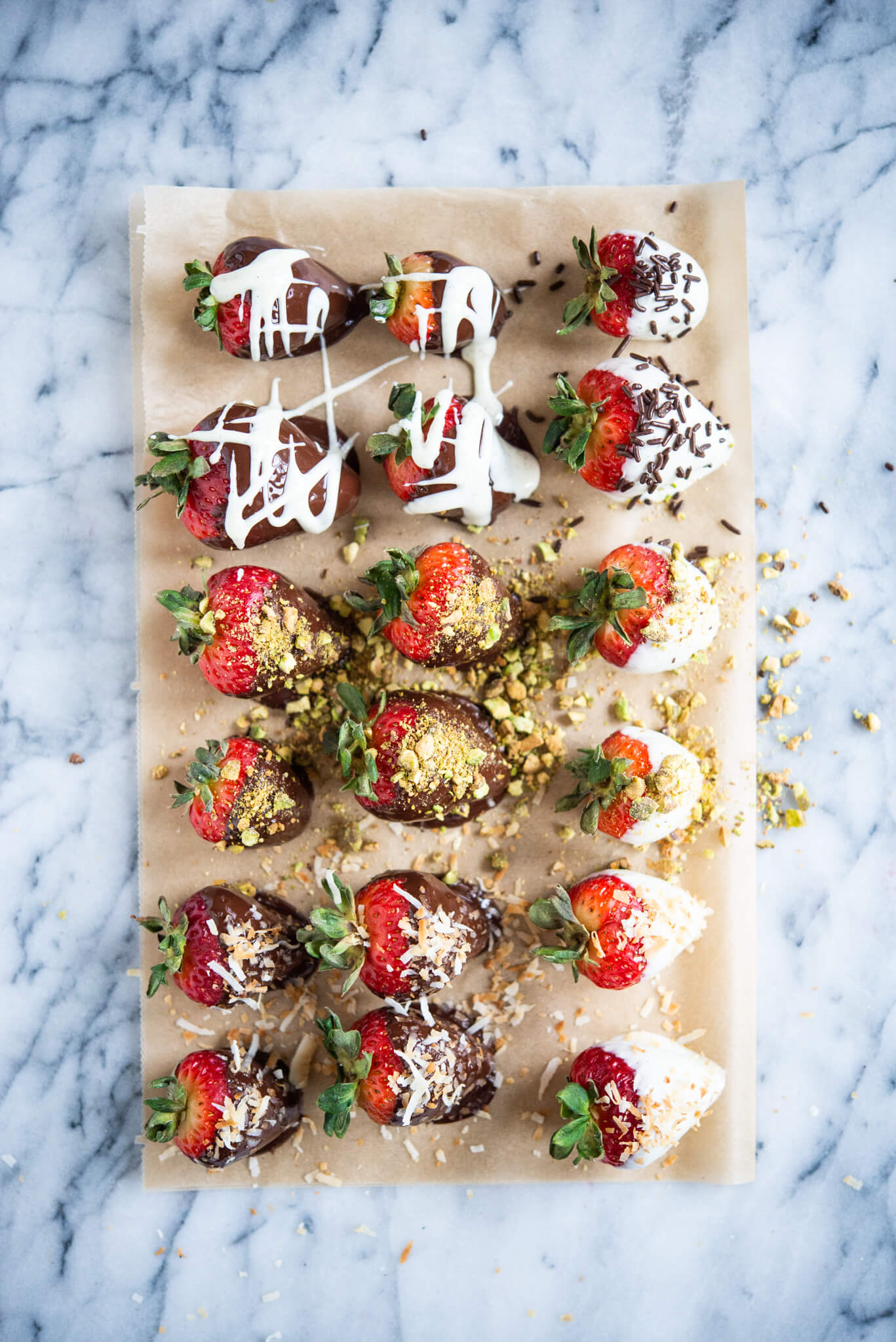 white and dark chocolate covered strawberries with different toppings on parchment paper on a marble surface